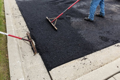 worker heating asphalt for a driveway parking lot